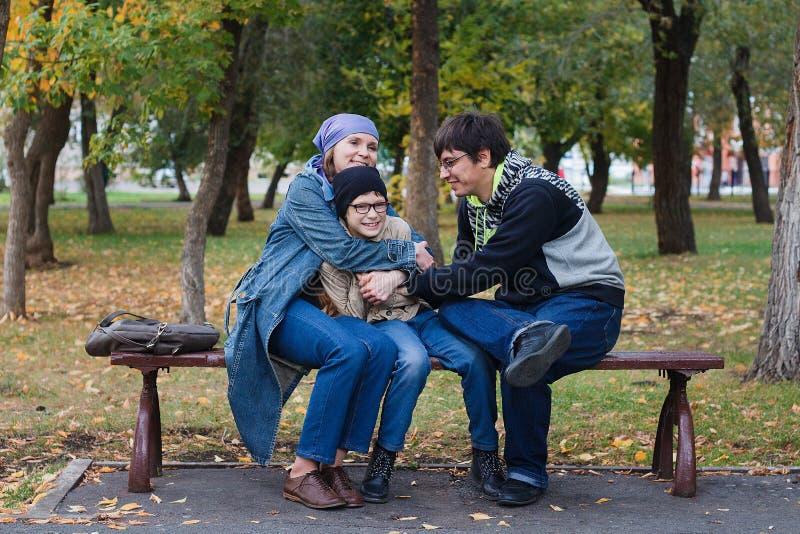 Kaukasische Spaßfamilie: Vati, Mutter und ihr Sohn sitzen auf einer Bank im Park im Herbst stockfoto