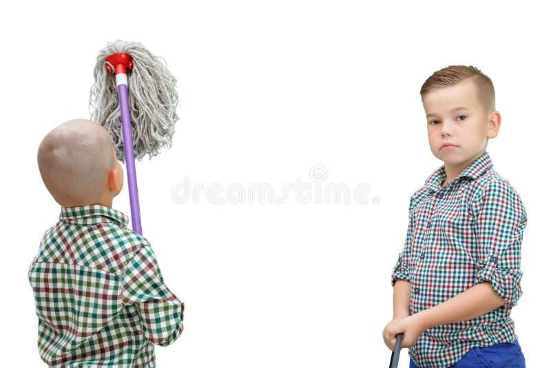 Kaukasische Stellung des Jungen zwei auf einem weißen lokalisierten Hintergrund und Halten eines Eimers des Wassers und des MOPS  lizenzfreies stockfoto