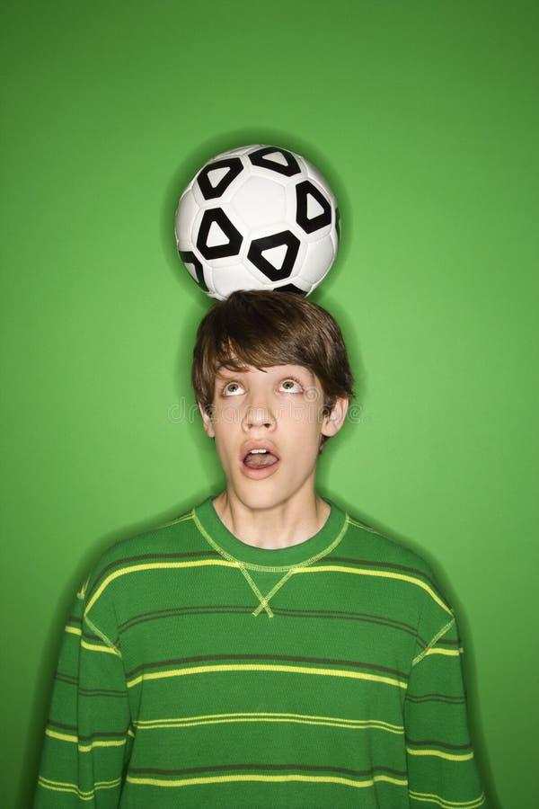 Kaukasische tienerjongen met voetbalbal op hoofd. stock fotografie