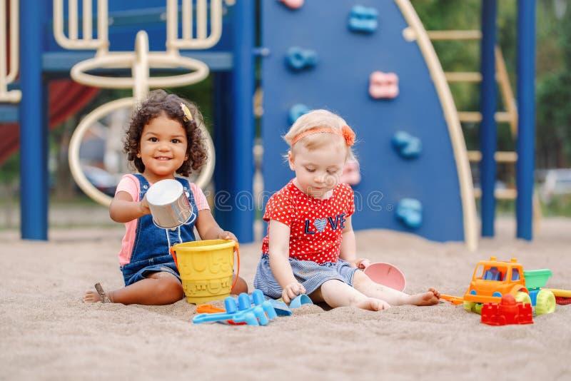 Kaukasische und hispanische lateinische Babykinder, die beim Sandkastenspielen sitzen stockbild