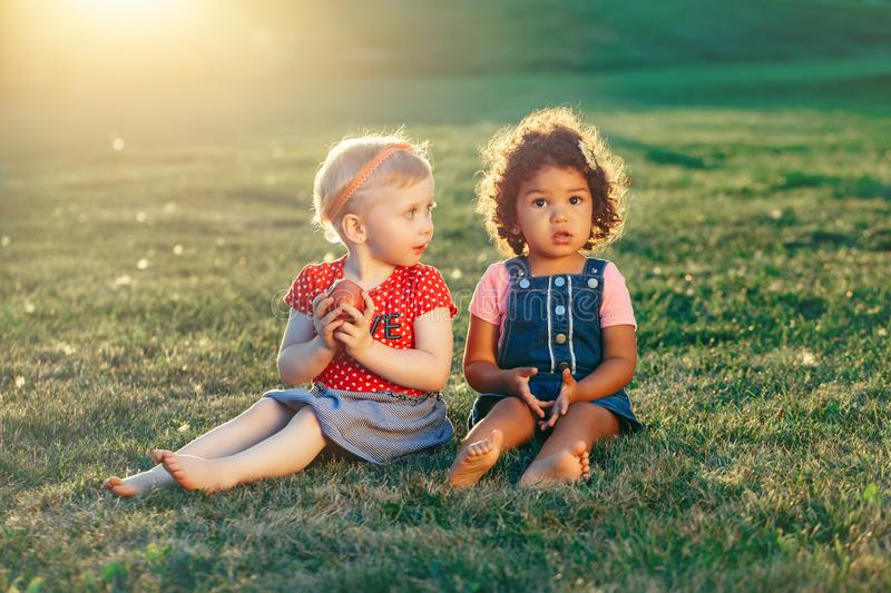 Kaukasische und lateinische hispanische Mädchenkinder, die Apfel sitzen zusammen, teilend stockfotografie