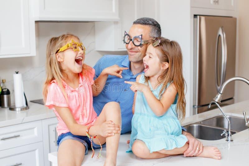 Kaukasische vaderpapa met twee kinderendochters die grappige glazen dragen en bij elkaar lachen stock afbeeldingen