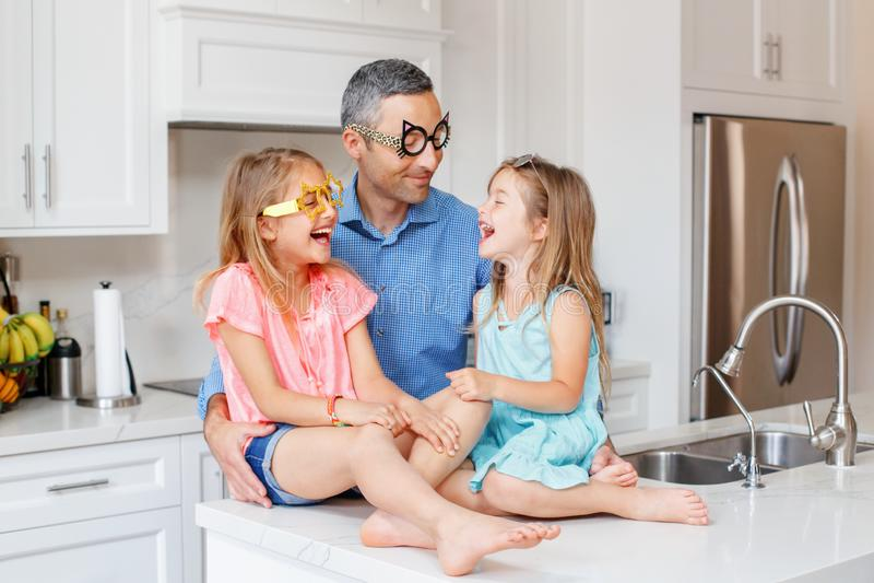 Kaukasische vaderpapa met twee kinderendochters die grappige glazen dragen en bij elkaar lachen stock fotografie
