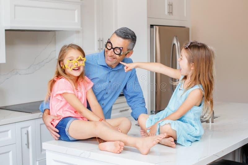Kaukasische vaderpapa met twee kinderendochters die grappige glazen dragen en bij elkaar lachen royalty-vrije stock afbeelding
