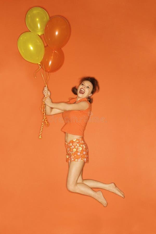 Kaukasische vrouw die in lucht door ballons wordt opgeheven. royalty-vrije stock afbeelding