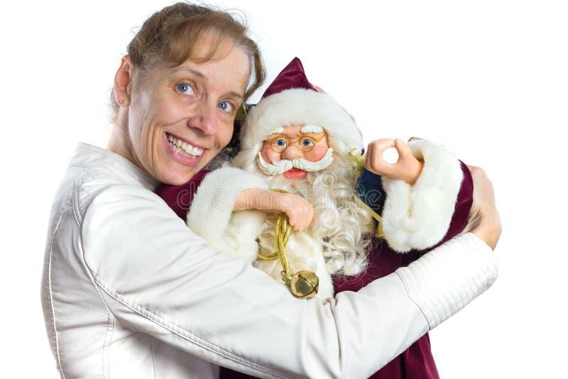 Kaukasische vrouw die Santa Claus omhelzen bij Kerstmis stock fotografie