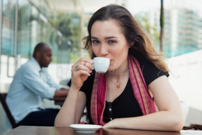 Kaukasische vrouw die van een kop van koffie in een restaurant genieten stock fotografie