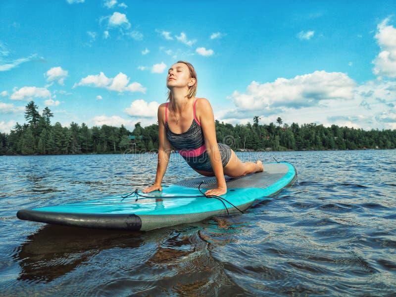 Kaukasische vrouw die yoga op de peddelsup van het meerwater raad doet bij zonsondergang stock afbeeldingen