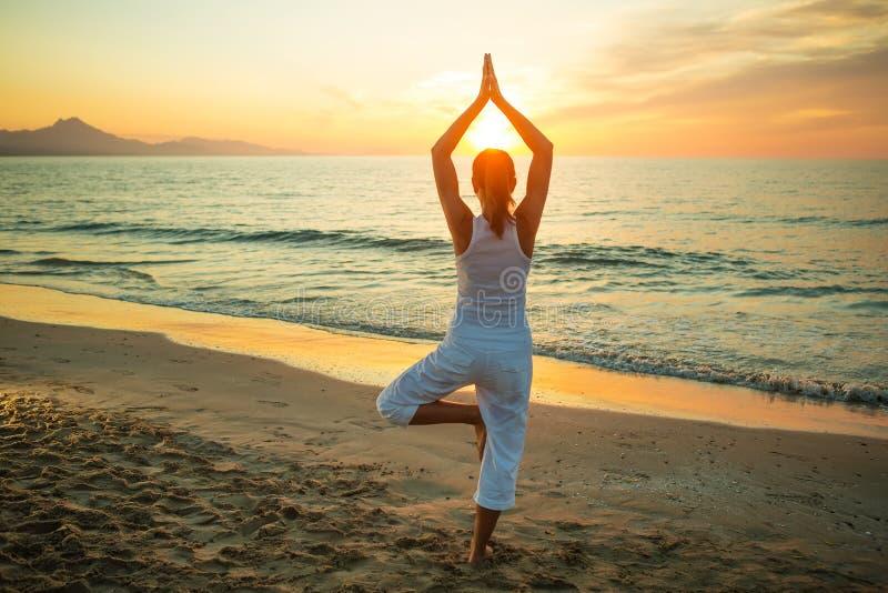 Kaukasische vrouw het praktizeren yoga bij kust royalty-vrije stock afbeeldingen