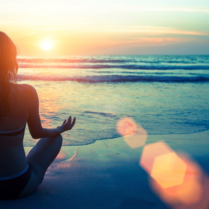Kaukasische vrouw het praktizeren yoga bij kust tijdens zonsondergang ontspan stock afbeeldingen