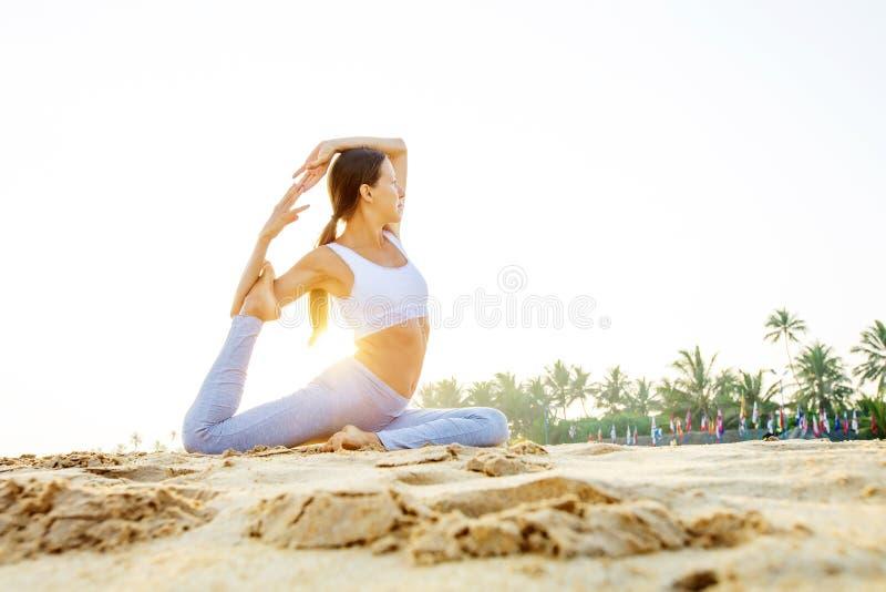 Kaukasische vrouw het praktizeren yoga bij kust van tropische oceaan stock foto's