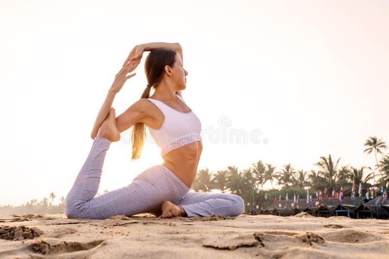 Kaukasische vrouw het praktizeren yoga bij kust van tropische oceaan royalty-vrije stock afbeeldingen