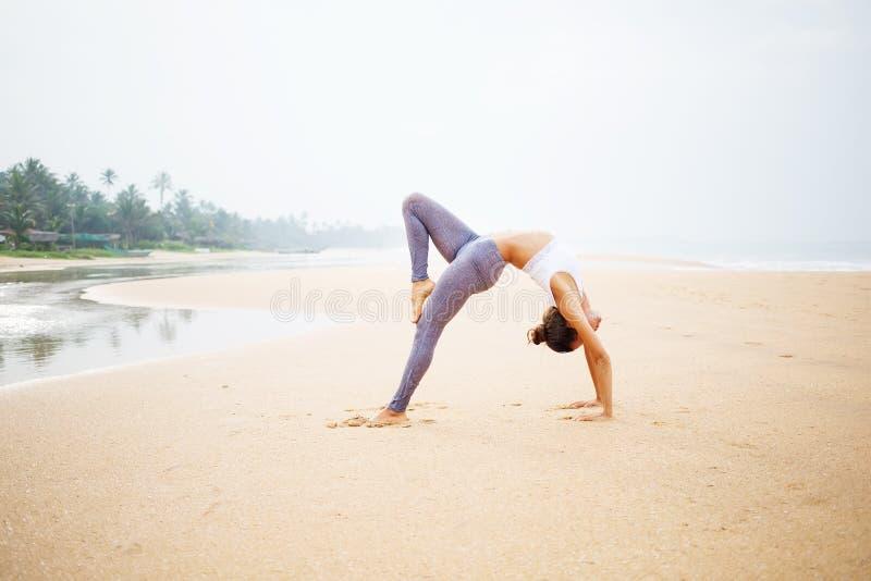 Kaukasische vrouw het praktizeren yoga bij kust van tropische oceaan stock afbeelding