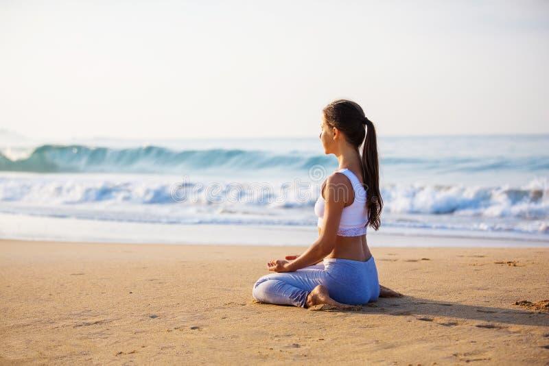 Kaukasische vrouw het praktizeren yoga bij kust van tropische oceaan royalty-vrije stock afbeelding