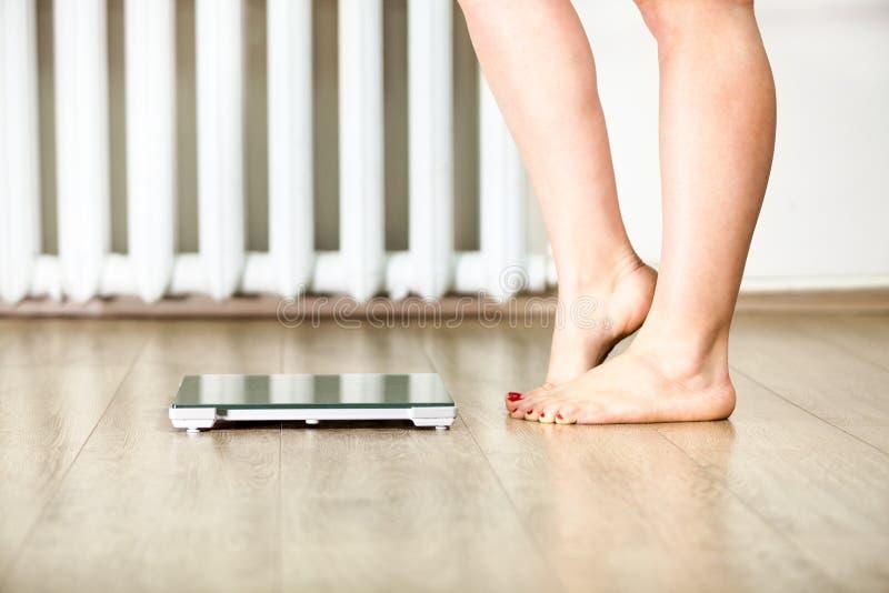 Kaukasische vrouwelijke benen die zich voor gewichtsschalen bevinden die zich aarzelen te bevinden stock fotografie