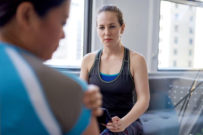 Kaukasische vrouwenfysiotherapeut die aan een medio-volwassen Chinese vrouwelijke patiënt spreken en nota's over een tablet nemen royalty-vrije stock afbeelding