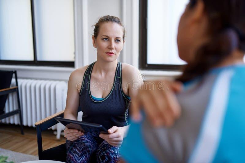 Kaukasische vrouwenfysiotherapeut die aan een medio-volwassen Chinese vrouwelijke patiënt spreken en nota's over een tablet nemen stock fotografie