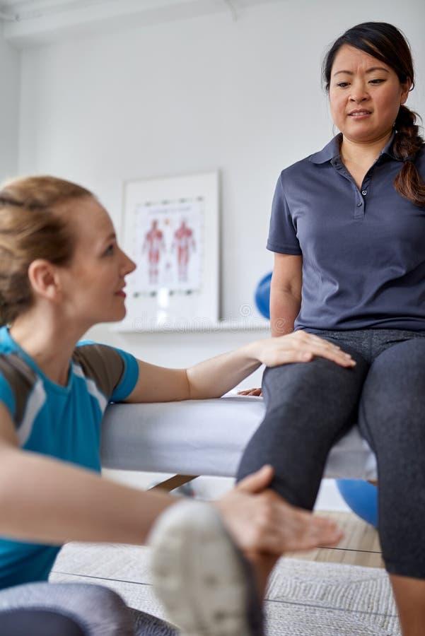 Kaukasische vrouwenfysiotherapeut die het been en de knie van een medio-volwassen Chinese vrouwelijke geduldige zitting op een ma stock afbeeldingen