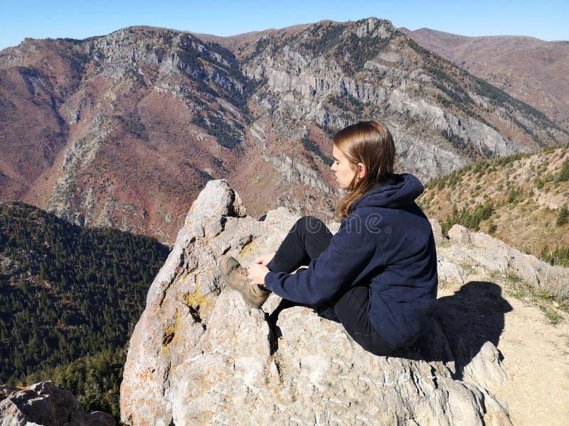 Kaukasische wandelaar die haar laarzen vastbindt, zit aan de top van de berg royalty-vrije stock foto's