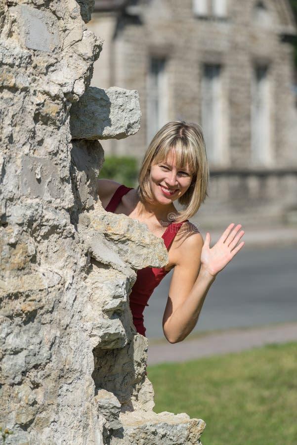 Kaukasische witte vrouwelijke model en baksteensteen Vrouw in een rode kleding die zich achter de muur in het stadspark bevinden stock fotografie