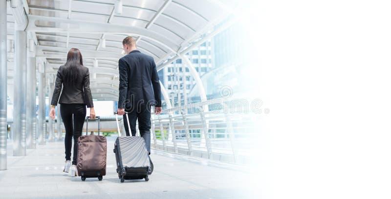 Kaukasische zakenman en zakenvrouw wandelen samen met bagage op de openbare straat met kopieerruimte, reisconcept voor bedrijven stock fotografie