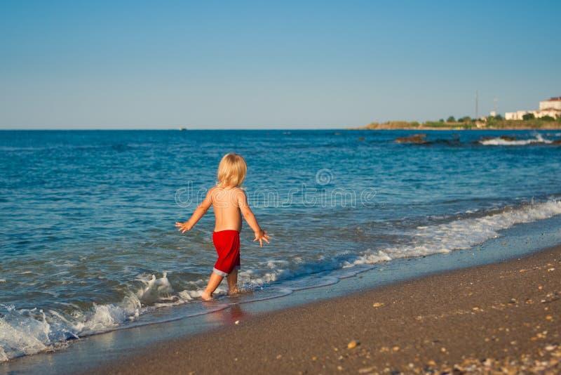 Kaukasischer Babyweg auf dem Strand stockfotos