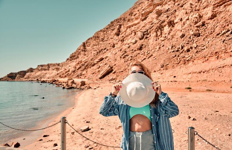 Kaukasischer gebräunter Haut Frauen-großer Hutstand auf Dock des Yacht-Bootes unter blauem Himmel des Sommers im Ferienfeiertag m lizenzfreie stockfotos