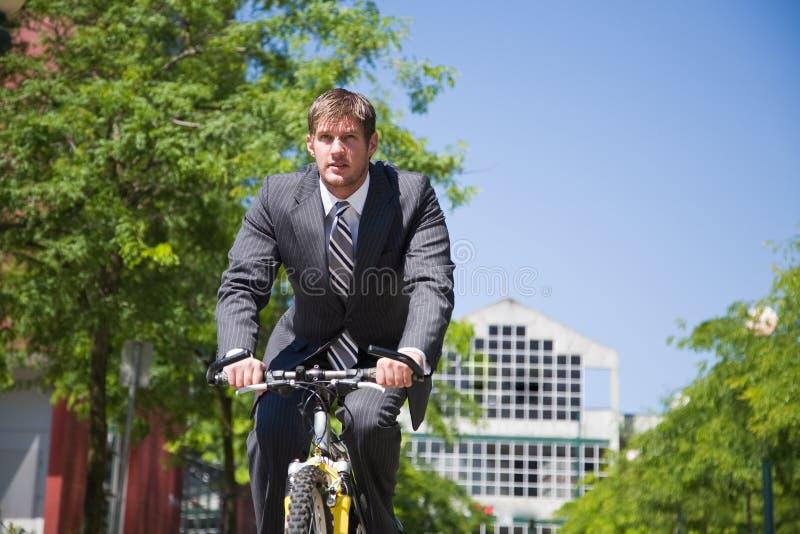 Kaukasischer Geschäftsmann, der Fahrrad fährt lizenzfreies stockbild