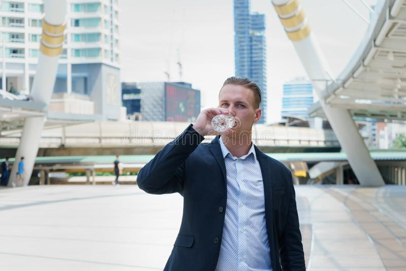 Kaukasischer Geschäftsmann, der reines Mineralwasser von der Plastikflasche in der Stadt trinkt stockfotografie