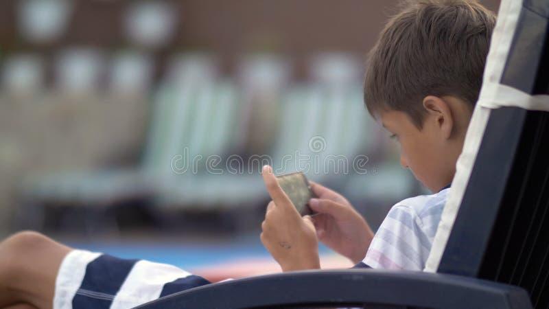 Kaukasischer jugendlich Junge, der an funktionierendem Handy des Ruhesessels am Swimmingpool liegt lizenzfreie stockbilder