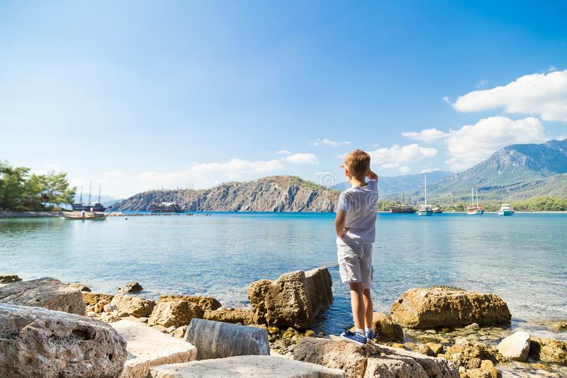 Kaukasischer Junge in einem weißen T-Shirt und in weißen kurzen Hosen kostet durch das Meer an Land am Sommernachmittag und schau lizenzfreie stockbilder