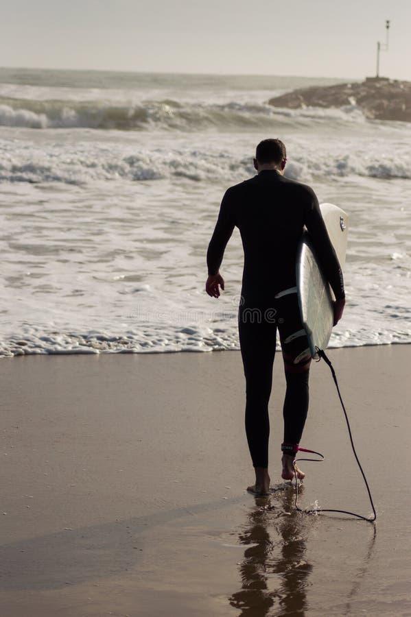 Kaukasischer Junge mit einem schwarzen Neopren zum Surfen bereit lizenzfreie stockfotografie