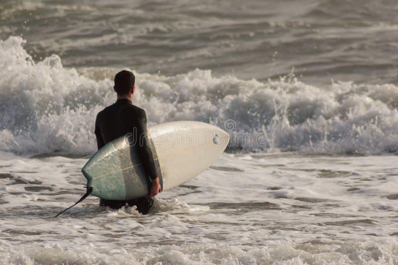 Kaukasischer Junge mit einem schwarzen Neopren zum Surfen bereit lizenzfreie stockbilder