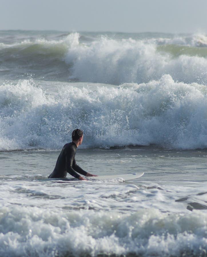 Kaukasischer Junge mit einem schwarzen Neopren zum Surfen bereit stockbild