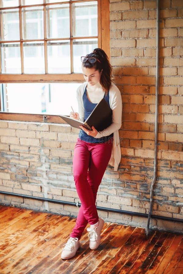Kaukasischer junger brunette weiblicher zeichnender Designerk?nstler der Studentin in der Halle der Collegeuniversit?t stockbilder
