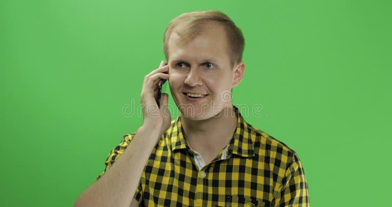 Kaukasischer junger Mann im gelben Hemd unter Verwendung des Handys für Anruf lizenzfreie stockfotografie