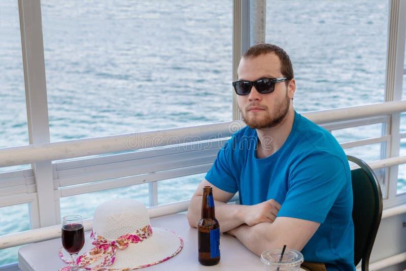 Kaukasischer Mann, der auf dem Boot trinkt ein Bier sitzt lizenzfreie stockfotografie