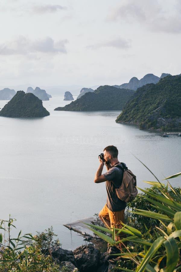 Kaukasischer Mann, der ein Foto auf eine Oberseite einer Klippe übersieht Halong-Bucht während des Sonnenuntergangs, Vietnam mach stockfoto