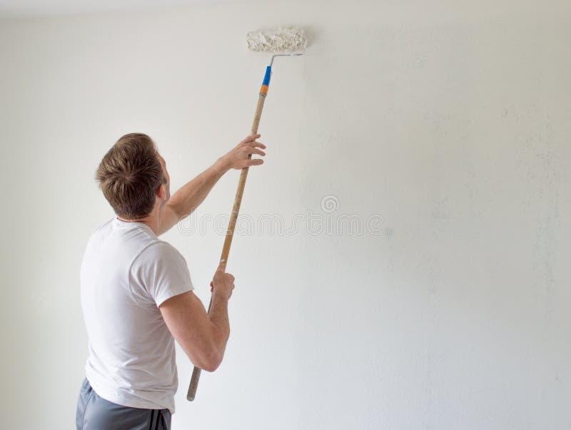 Kaukasischer Mann, der eine Wand mit einer Farbenrolle malt stockbild