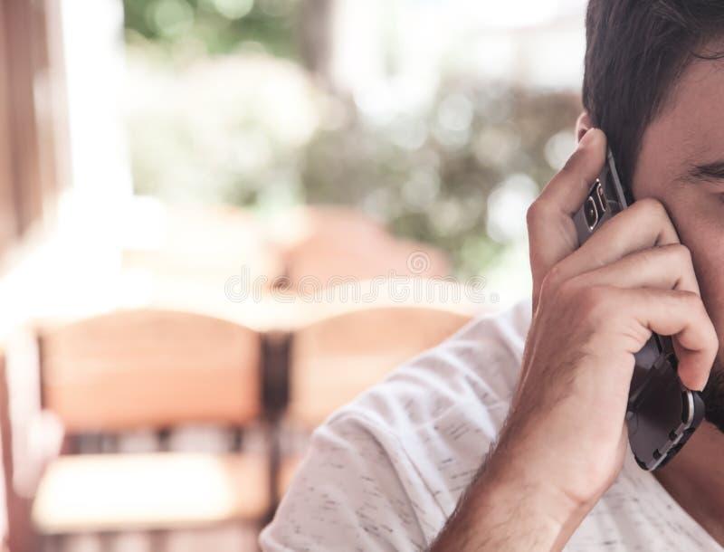 Kaukasischer Mann, der in einem Café spricht am Telefon sitzt stockfotos