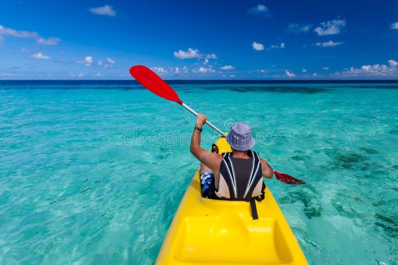 Kaukasischer Mann, der im Meer bei Malediven Kayak fährt lizenzfreies stockfoto