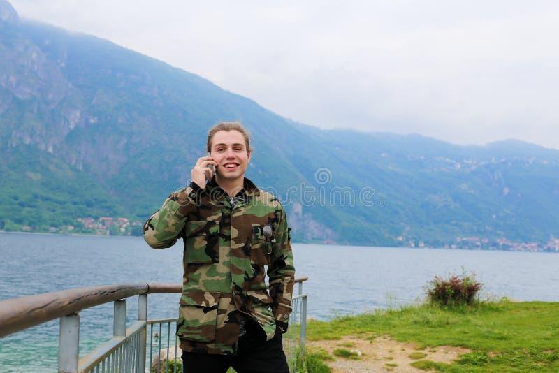Kaukasischer Mann, der mit Smartphone in der Nähe von Banister, See Como und Alpen im Hintergrund spricht stockfoto