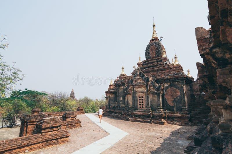 Kaukasischer Mann, der nahe bei dem buddhistischen Tempel von Bagan, Myanmar geht stockfoto