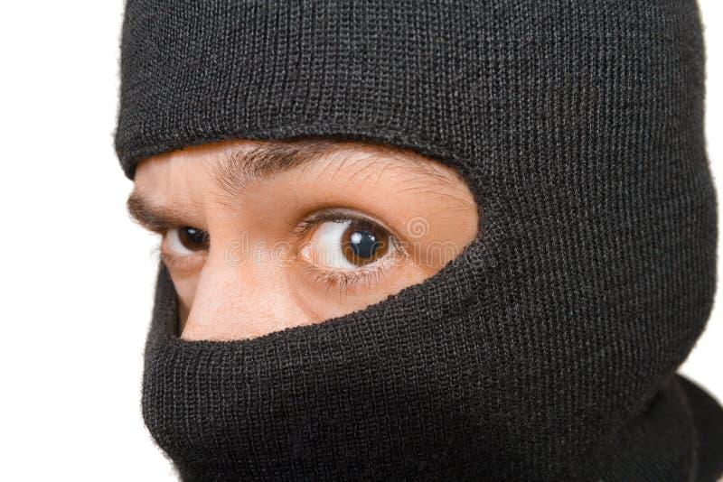 Kaukasischer Mann in der schwarzen Maske schaut zur Kamera stockbild