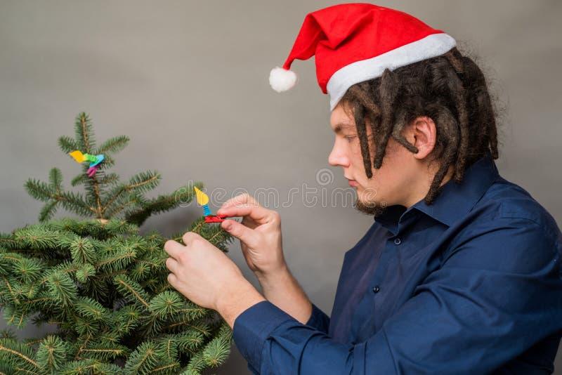 Kaukasischer Mann mit Dreadlocksfrisur und haning Dekorationen Sankt-Hutes auf charistmas Baum stockbild