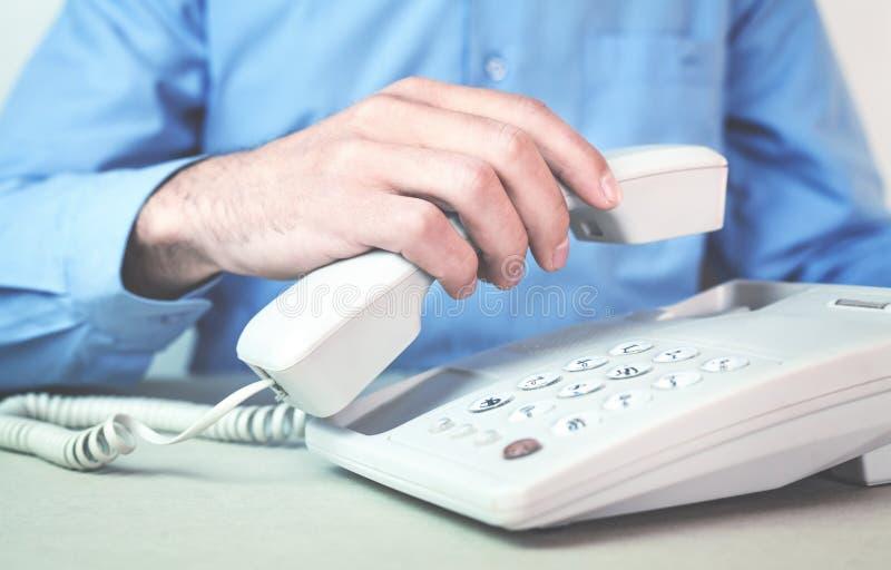 Kaukasischer Mann mit einem örtlich festgelegten Telefon lizenzfreie stockfotografie