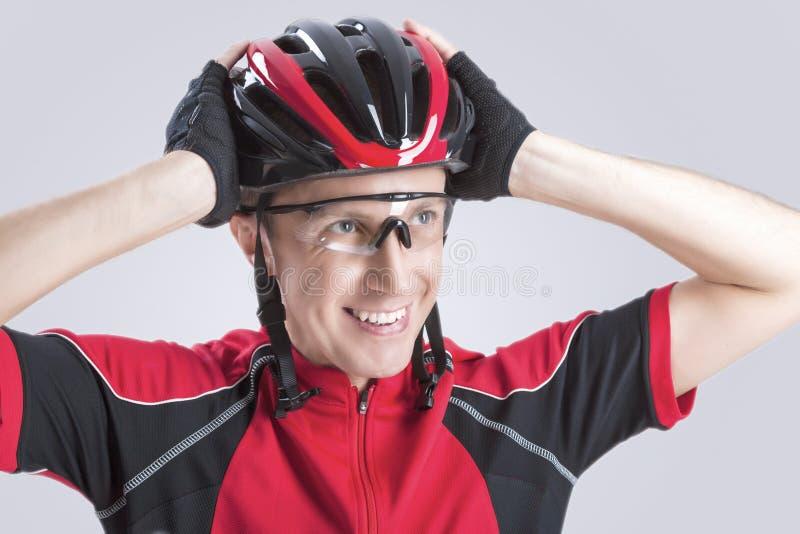 Kaukasischer Radfahrer, der Straßen-Sturzhelm überprüft lizenzfreie stockbilder