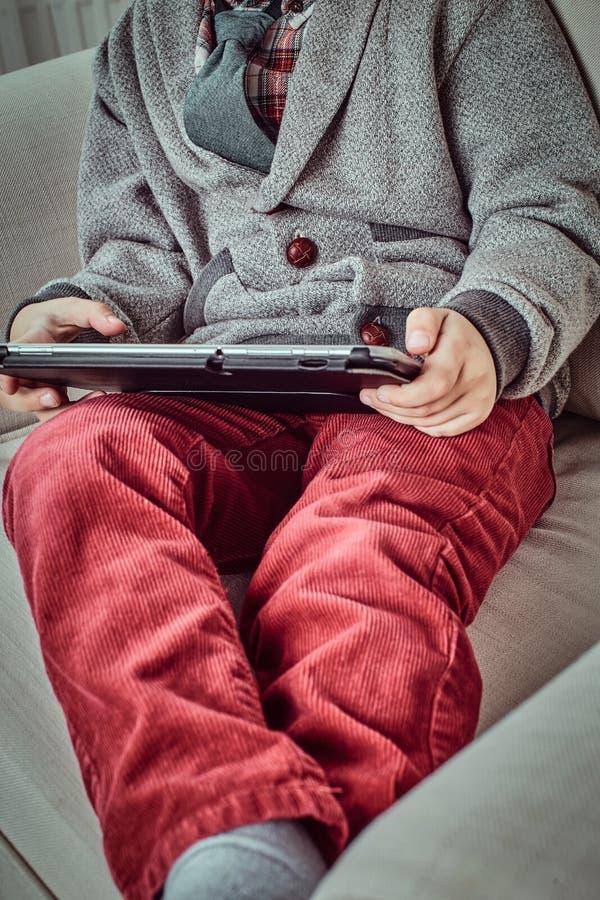 Kaukasischer Schüler, der elegante Kleidung unter Verwendung einer digitalen Tablette beim auf einer Couch zu Hause sitzen trägt stockbilder