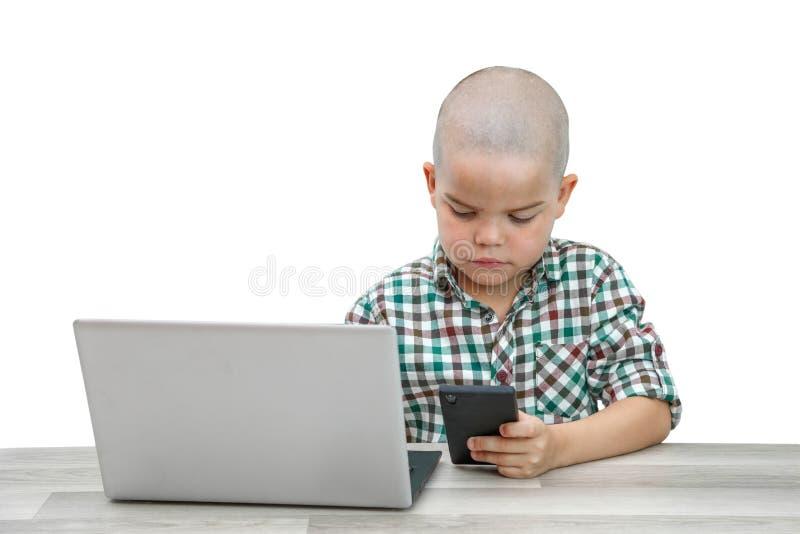 Kaukasischer schulpflichtiger Junge in einem karierten Hemd auf einem hellen lokalisierten Hintergrund, der Spiele am Telefon und lizenzfreies stockbild