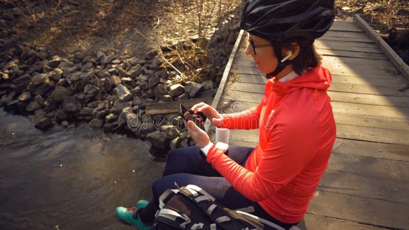 Kaukasischer Sportfrauenradfahrer, der Musik in den drahtlosen weißen Kopfhörern herein sitzen auf einer Holzbrücke über einem kl lizenzfreies stockbild